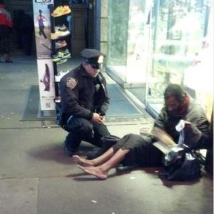 30/11/2012 - Policial de Nova York fica famoso após ser fotografado dando botas a mendigo