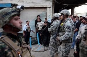 Soldados norte-americanos observam explosões em Kirkuk (Iraque), sem reagir. De acordo com a nova estratégia dos Estados Unidos, os militarem só podem agir se a polícia iraquiana solicitar
