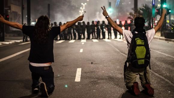 11jun2013-manifestantes-se-ajoelham-diante-de-pms-durante-protesto-na-avenida-paulista-em-sao-paulo-o-homem-da-esquerda-foi-atingido-por-uma-bala-de-borracha-na-sequencia-1371005432910