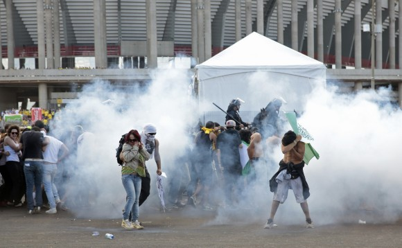 Activists and students stand in a cloud of tear gas as they clash with riot police outside the Mane Garrincha National Stadium in Brasilia