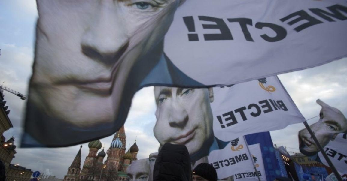 Multidão realiza passeta em apoio à anexação da Crimeia a Rússia com faixas que mostram o presidente russo Vladimir Putin na praça Vermelha em Moscou FOTO  Pavel Golovkin AP
