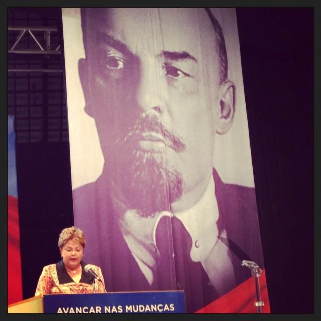 Dilma discursando com a imagem de Lenin atrás