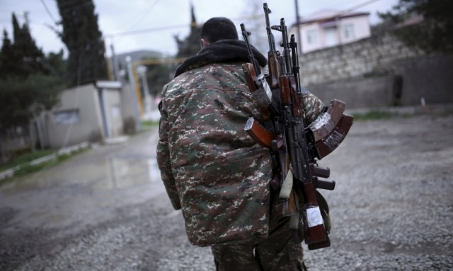 A soldier of the self-defense army of Nagorno-Karabakh carries weapons in Martakert province, which according to Armenian media was affected by clashes over the breakaway Nagorno-Karabakh region, April 4, 2016. REUTERS/Vahan Stepanyan/PAN Photo